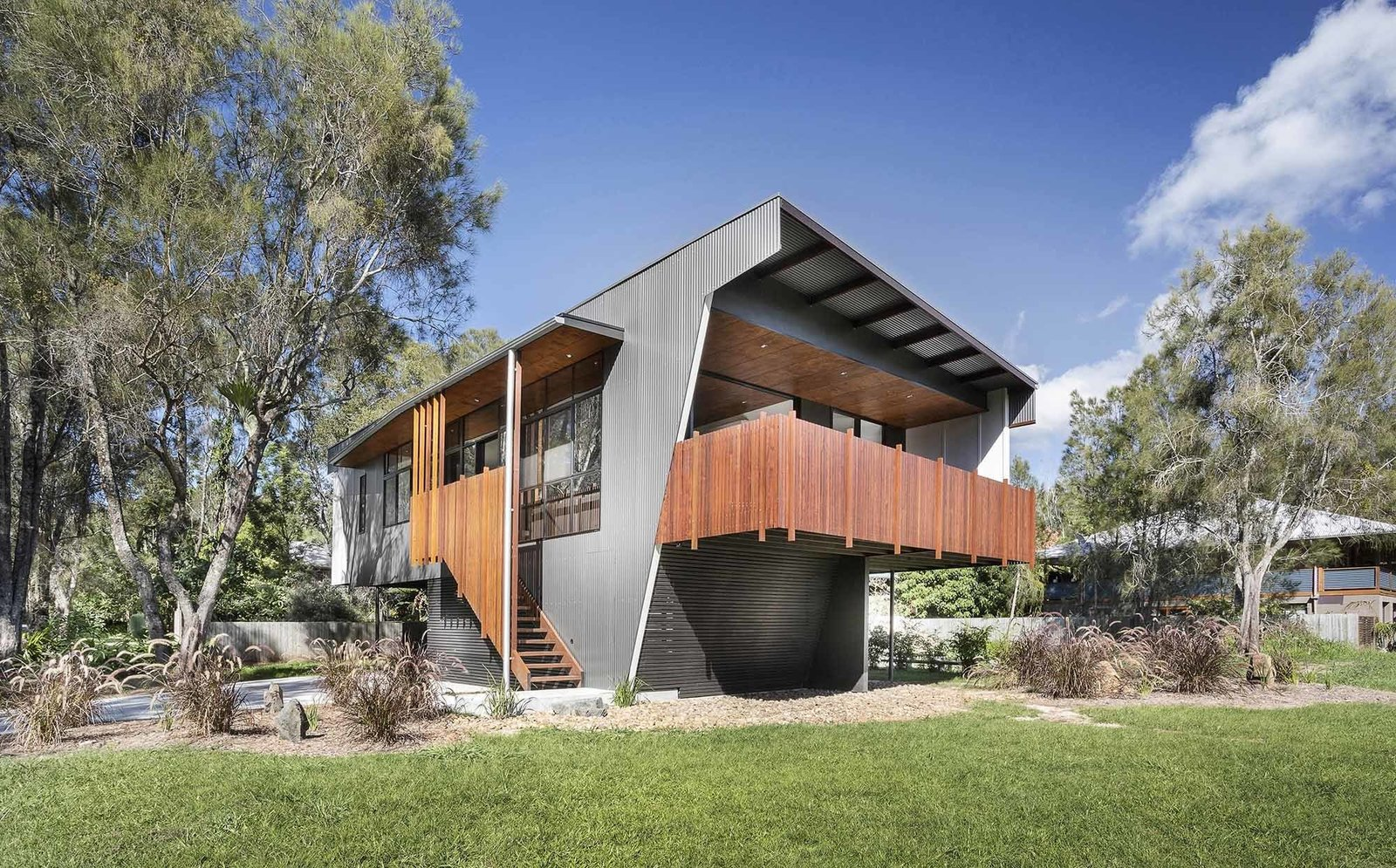 """The architects' inventive use of resources helped keep costs down. """"We gave the facade's ribbed metal cladding, commonly used in neighboring beach shacks, a metallic finish that provided a cost-effective solution and an upscale appearance,"""" Rathmayr says. Tagged: Outdoor, Back Yard, and Grass.  Northern Rivers Beach House by Tiffany Jow"""