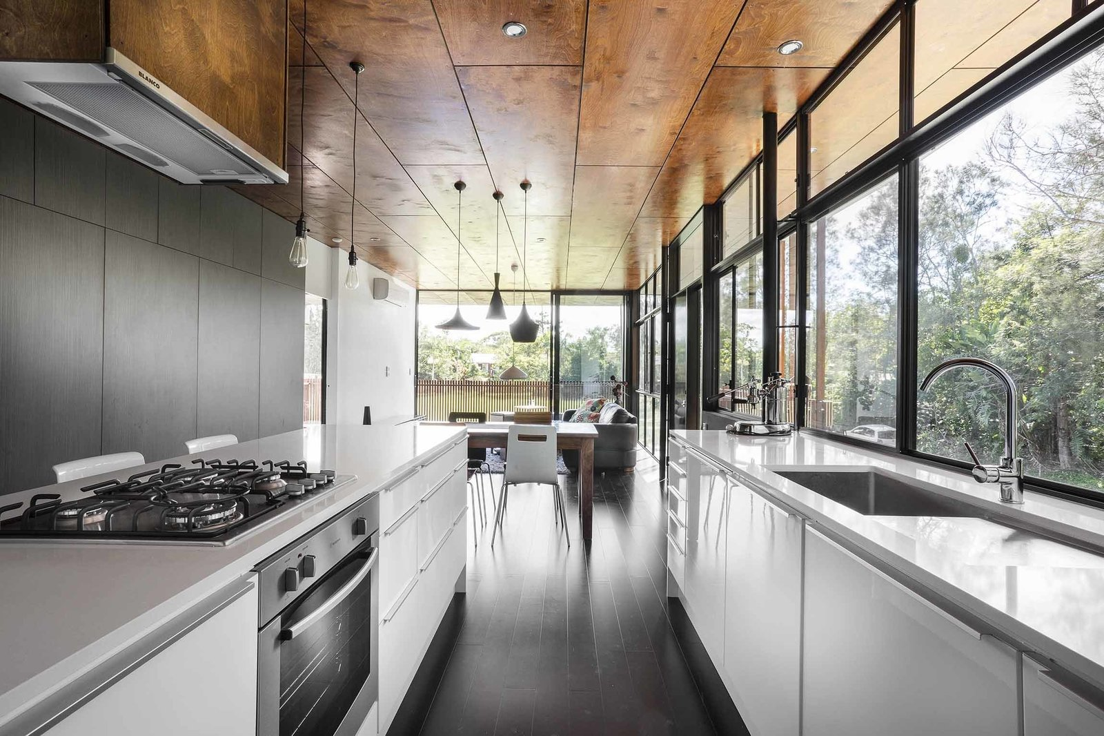 In the kitchen, a Blanco exhaust fan is surrounded by a stove, oven, and dishwasher by Westinghouse. A series of pendants by She Lights are equipped with LED fittings. Tagged: Kitchen, White Cabinet, Pendant Lighting, Range, and Undermount Sink. Northern Rivers Beach House by Tiffany Jow