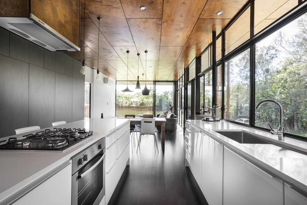 In the kitchen, a Blanco exhaust fan is surrounded by a stove, oven, and dishwasher by Westinghouse. A series of pendants by She Lights are equipped with LED fittings.