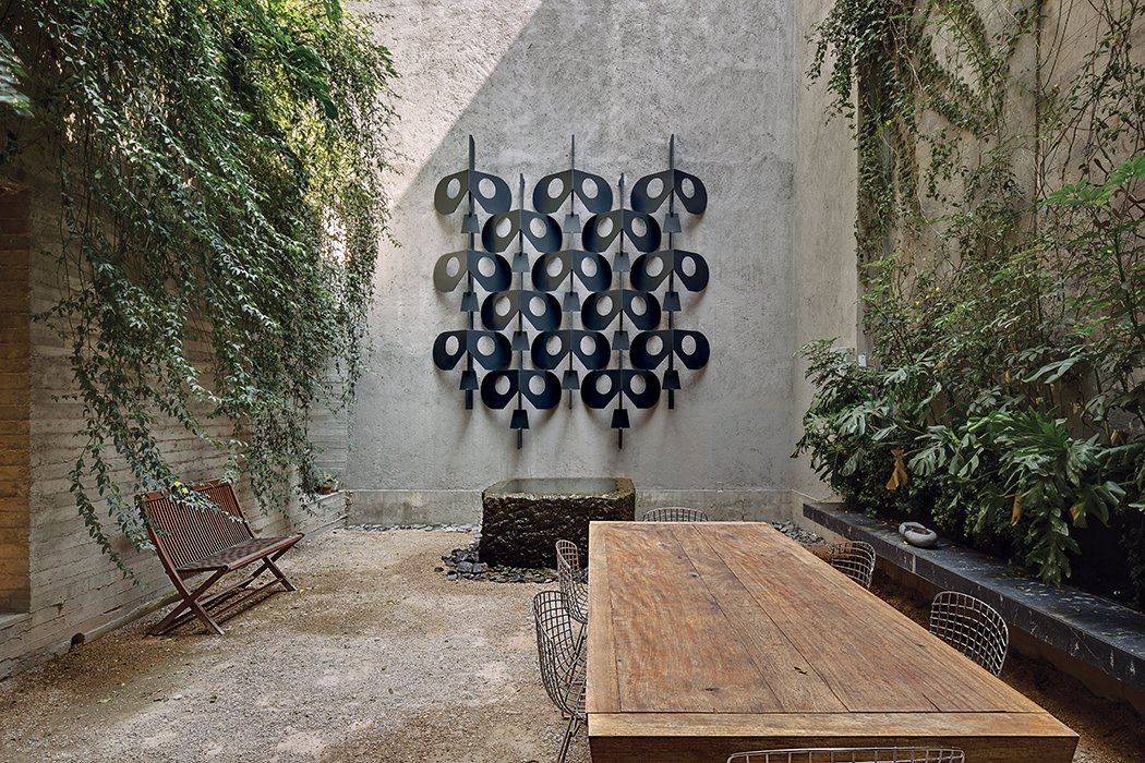 The house features several courtyards, conveying an ever-present sense of indoor-outdoor living. Concrete walls are lined with yellow jasmine, and the wall sculpture is taken from Manuel Felguérez's fence for the National Anthropology Museum.