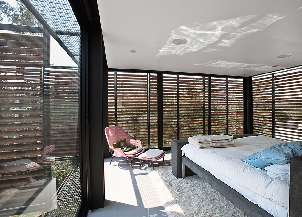 The master bedroom is shaded by exterior slats in cumaru, a sustainable tropical wood. Alazraki designed the custom bed frame. Tagged: Bedroom, Chair, Bed, Ceiling Lighting, Recessed Lighting, and Rug Floor.  Photo 5 of 6 in A Sublime Indoor/Outdoor Retreat in Mexico City
