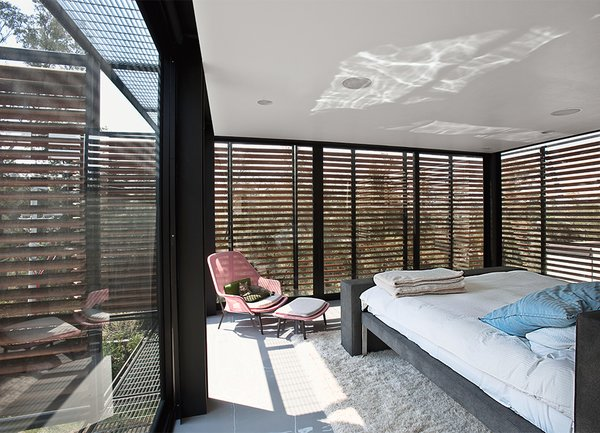 The master bedroom is shaded by exterior slats in cumaru, a sustainable tropical wood. Alazraki designed the custom bed frame.
