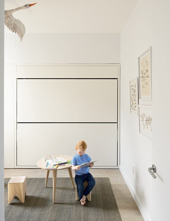How One Family of Three Does It All in 675 Square Feet - Photo 4 of 14 - In his room, Finn sits on a Stump stool by Kalon Studios at an oak table from Canvas Home. The flat jute rug is from ABC Carpet & Home; the stainless-steel door hardware is by Emtek.