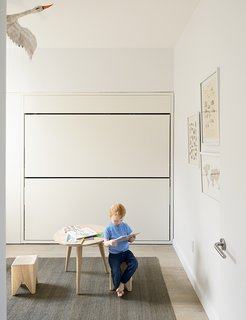 In his room, Finn sits on a Stump stool by Kalon Studios at an oak table from Canvas Home. The flat jute rug is from ABC Carpet & Home; the stainless-steel door hardware is by Emtek.