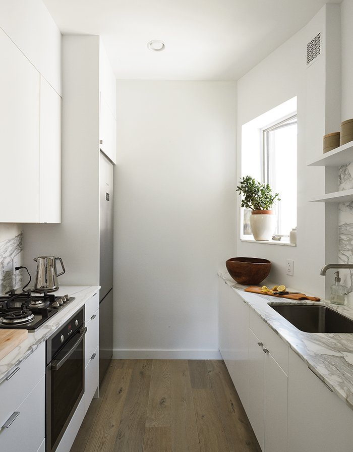 In the new space, small-scale, 24-inch appliances from Fagor are incorporated into Ikea's Applåd cabinetry. Tagged: Kitchen, Refrigerator, Range, Undermount Sink, Marble Counter, Medium Hardwood Floor, and White Cabinet.  Photo 12 of 14 in How One Family of Three Does It All in 675 Square Feet