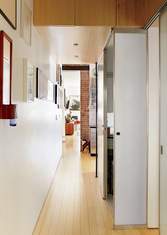 """Encased in Panelite, the bathroom creates a lantern effect when illuminated from within. """"At night it's nice because you can put on the shower light, close that door, and it's like a floating box in the apartment,"""" McManus says. """"It just glows."""""""