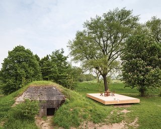 Dutch Military Bunker Becomes Tiny Vacation Home - Photo 1 of 2 - Architect Bruno Despierre built a deck for outdoor activities from pine wood.