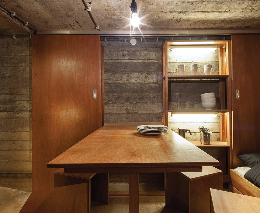 Custom-designed furniture outfits the interior of a bunker-turned-vacation retreat in the Netherlands. Tagged: Dining Room, Bench, and Concrete Floor.  Photo 2 of 2 in Dutch Military Bunker Becomes Tiny Vacation Home