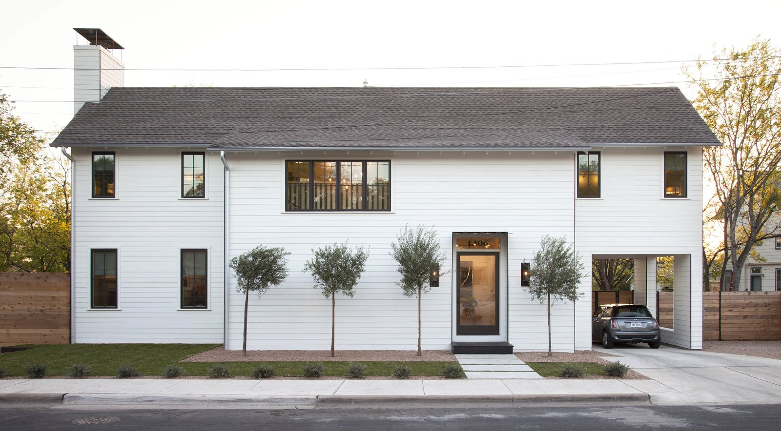The exterior of the new, two-story home in East Austin, Texas was designed with a minimal palette, bronze windows, and steel details in order to blend into the existing cityscape. Tagged: Exterior, House, Shingles Roof Material, and Wood Siding Material.  Photo 1 of 8 in Modern Take on a Texas Farmhouse