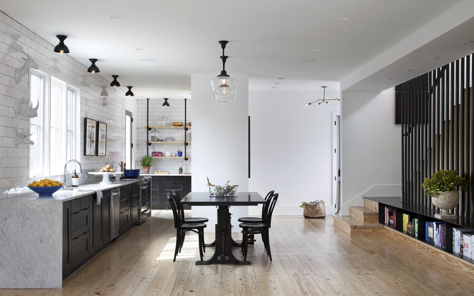 The kitchen and adjoined dining space have a light, open feel, as does the rest of the home. Complementary design elements, like the low-slung steel bookcase next to the stairs, which Flournoy's partner organized according to color, reappear throughout the house. Pops of color add an appealing break from the largely monochromatic palette, and reinforce the couple's design aesthetic. The Bistro chairs are from Crate and Barrel.