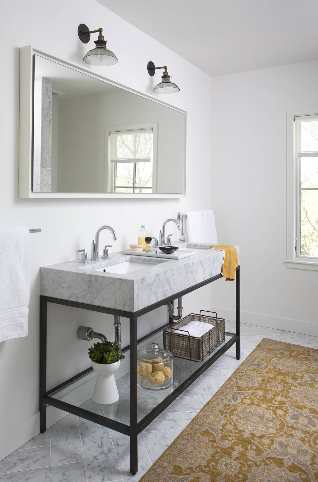"""White walls, a luxurious marble double-sink, and an area rug give this bathroom an inviting atmosphere. """"The natural light, open spaces, and light color palette make it a great place to wake up in the morning,"""" Flournoy says of his home. The sink is from Restoration Hardware and the rug is from West Elm. Tagged: Bath Room, Marble Counter, Marble Floor, Wall Lighting, Undermount Sink, and Rug Floor.  Photo 7 of 8 in Modern Take on a Texas Farmhouse"""