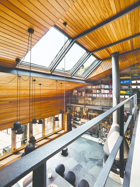 Structural changes were immediately made to the original shell to bring in more natural light. The small windows on the front façade were dramatically replaced with a folding window assembly that stretches the entire width of the room. Skylights were cleverly added slightly beneath the peak pitch of the roof to funnel light towards the mezzanine, while still illuminating the main floor below. Warm, rich iroko wood spans the ceiling and wall, and also extends to the seating bench beneath the window.