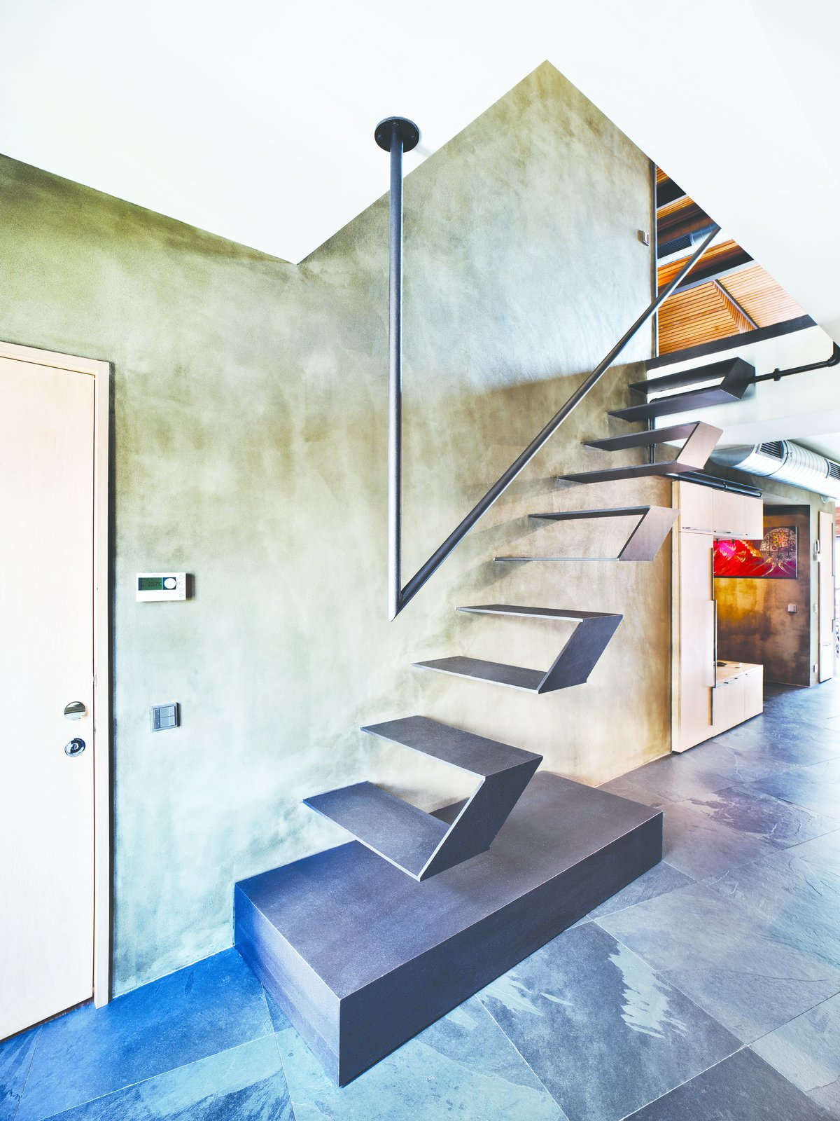 Futuristic floating stairs lead to the loft's mezzanine. Throughout the lower level, natural stone was chosen for the flooring, laid at an irregular angle to add visual interest. Tagged: Staircase, Metal Railing, and Metal Tread.  Loft by Paolo Rivera from A Single-Room Loft with Impressive Wall-to-Wall Storage