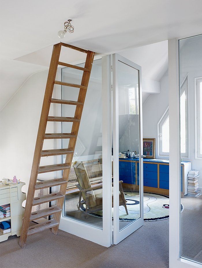 A ladder leads to a guest room in the attic. The striking-blue bedroom dresser was part of a modular storage system installed by the previous owner. Tagged: Office, Study, Chair, Storage, and Library.  Photo 9 of 9 in This Petite Paris Apartment is a Vintage Furniture–Filled Delight