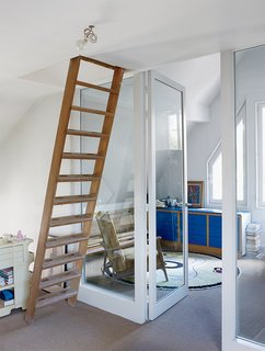 This Petite Paris Apartment is a Vintage Furniture–Filled Delight - Photo 9 of 9 - A ladder leads to a guest room in the attic. The striking-blue bedroom dresser was part of a modular storage system installed by the previous owner.