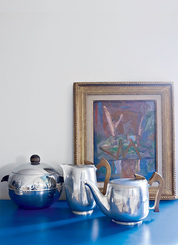Antique tea and chocolate pots are juxtaposed with a 1930s painting by Jacques Villon, Marcel Duchamp's brother.  Photo 6 of 9 in This Petite Paris Apartment is a Vintage Furniture–Filled Delight
