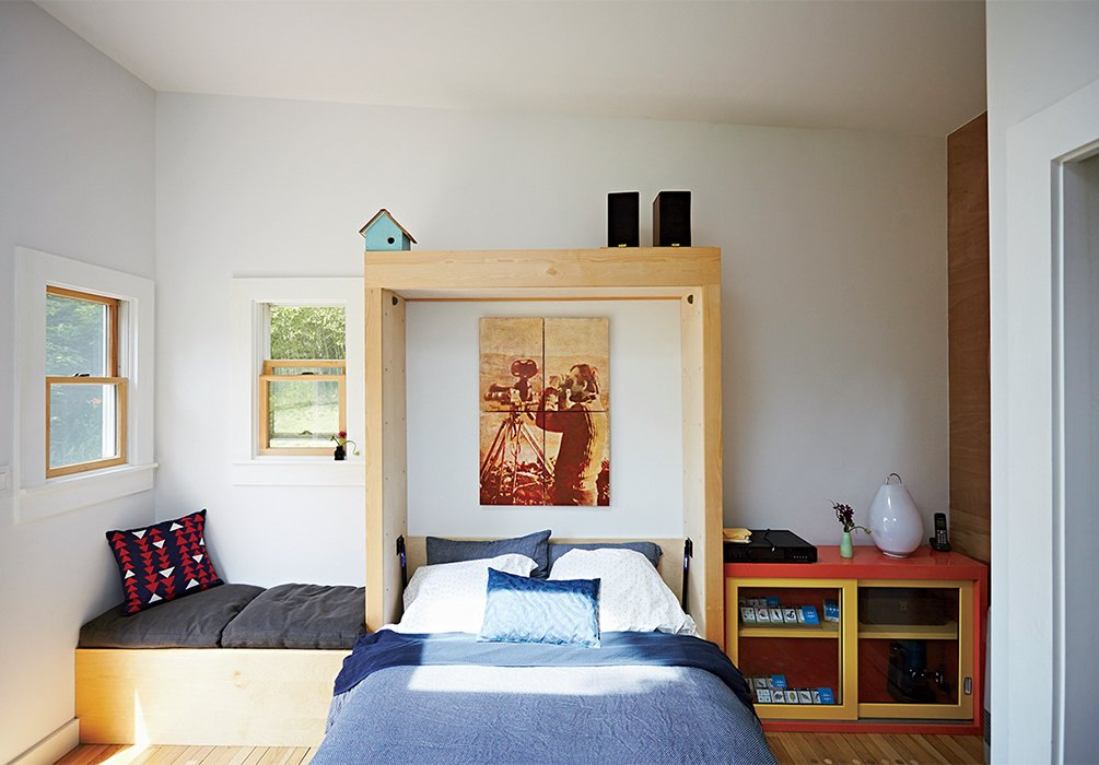 The outbuilding serves as a studio, a guest house, and a playroom. A Murphy bed sourced from Craigslist was customized with a birch surround to give it a built-in appearance.