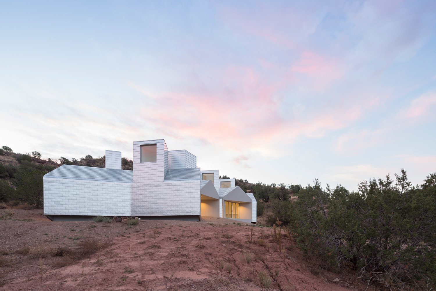 A small airspace separates the building's aluminum skin from the wall underneath. The aluminum acts like a heat sink during the day: it absorbs heat but remains thermally separated (by the narrow gap) from the Element House walls.  16+ Prefab Homes in the Middle of Nowhere by Luke Hopping from Prefab Units Cluster Together in this Off-the-Grid Guesthouse