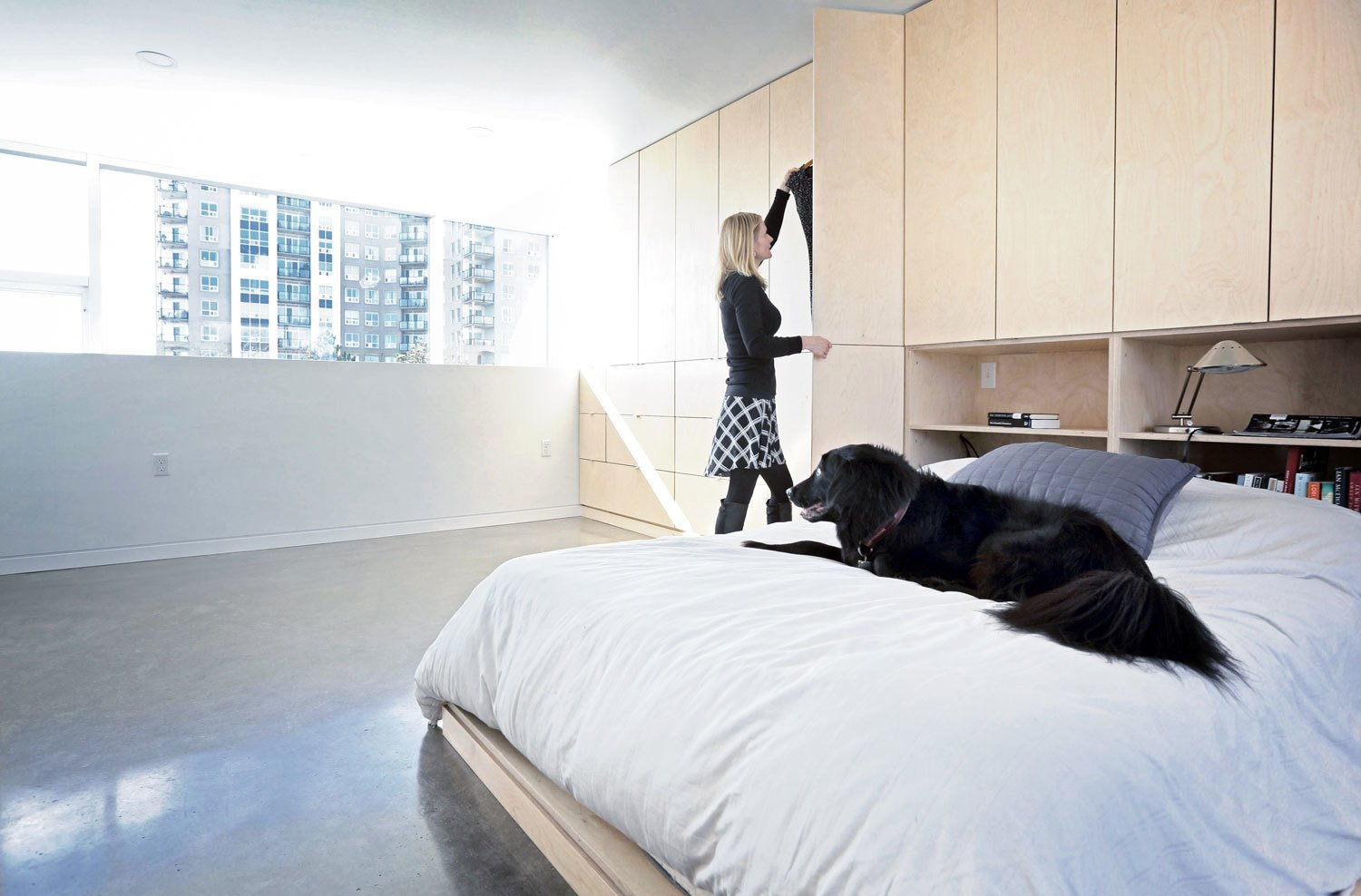 Concrete was chosen for both structural and finish material throughout much of the home, for its aesthetic, functional, and budgetary appeal. The polished concrete floors in the bedroom complement the birch bed and cabinetry. The home provides living space for the couple, two kids, one dog, and two cats. Tagged: Bedroom, Bed, Storage, Shelves, Concrete Floor, Recessed Lighting, Ceiling Lighting, and Table Lighting.  Photo 7 of 9 in The Architect Next Door