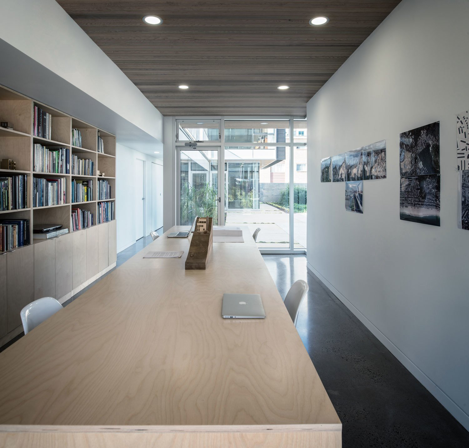 Positioned on the ground floor, the office enjoys spacial privacy, while still having intimate interaction with the living area above and common courtyard. Tagged: Office, Study, Shelves, Desk, Chair, and Bookcase.  Photo 9 of 9 in The Architect Next Door