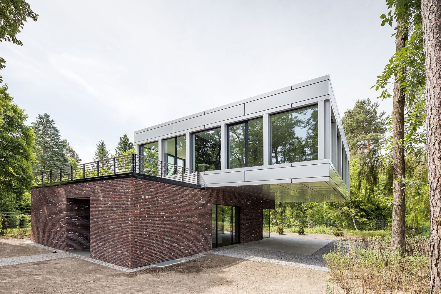 The lower level of this dramatically cantilevered house is covered in traditional red brick, while the upper level consists of coil-coated aluminium sheet with large glass panes.  Remarkable Brick Homes by Luke Hopping