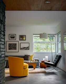 21 Enchanting Spaces That Feature Iconic Furniture - Photo 8 of 21 - In the living room, the architects painted the limestone fireplace a dark shade of blue-green. The walnut coffee table is by Noguchi for Herman Miller. The Barcelona chair is by Mies van der Rohe.