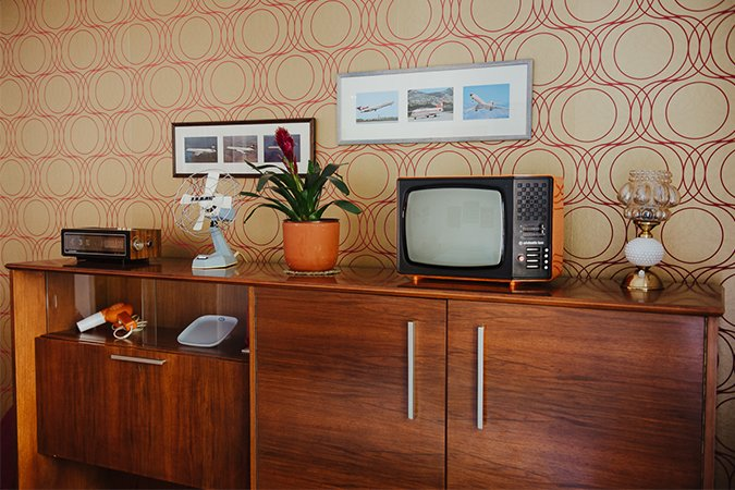 """""""The credenza is probably my favorite piece of furniture, and in the Yugodom I set up one in each room,"""" Milakovic says. The piece in the 1970s-themed bedroom features an array of period products that the former owner bought in Trieste, Italy, a favorite destination for buying """"Western"""" goods during the socialist era. All of the objects except the fan are marked Made in Yugoslavia. Dream Escapes That You Can Rent by Luke Hopping"""