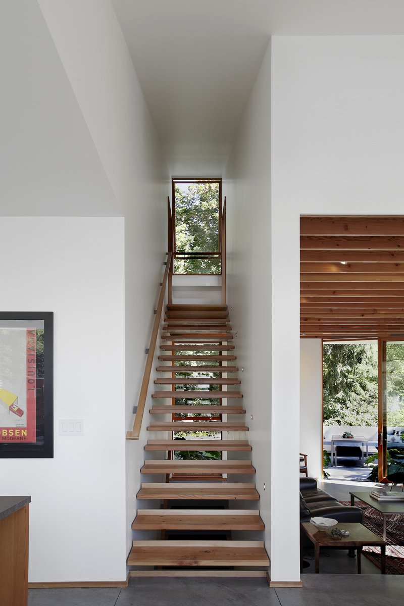 The architects divided the home into separate floors for sleeping, living, and working. Since the house is situated on a hill that slopes 20 feet from top to bottom, there are plenty of stairs. Those pictured above were crafted using wood salvaged from a 100-year-old bungalow that previously stood on the site.  Photo 2 of 11 in Seattle Home Carefully Blocks Out Neighbors, While Celebrating Natural Surroundings