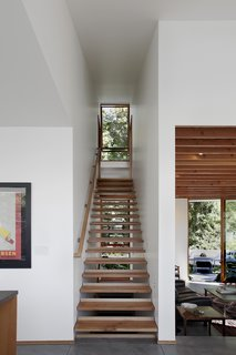 8 Beautiful Home Projects Using Reclaimed Wood - Photo 2 of 8 - A small, efficient home in Seattle designed by SHED Architecture & Design incorporated wood on the exterior and interior of the home, and even used salvaged wood from the residence that had previously stood on the site. Although the 100-year-old bungalow was demolished, the treads of one of its staircases were repurposed in the new home as a modern, open-riser stair that lets in light from the windows beyond.