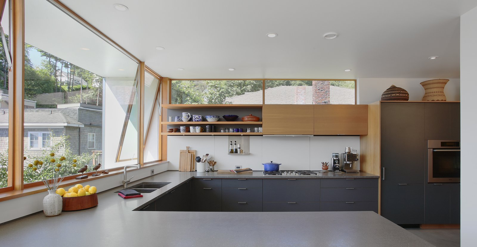 In the kitchen, a high western window carries the eye past neighboring rooftops to the lush hillside beyond. A wall also extends out to block sight of a neighboring deck. The architects paired custom shelving with slate-gray cabinets by Henrybuilt, cool Basaltina countertops, and white Corian backsplash. The faucet is by Cifial.