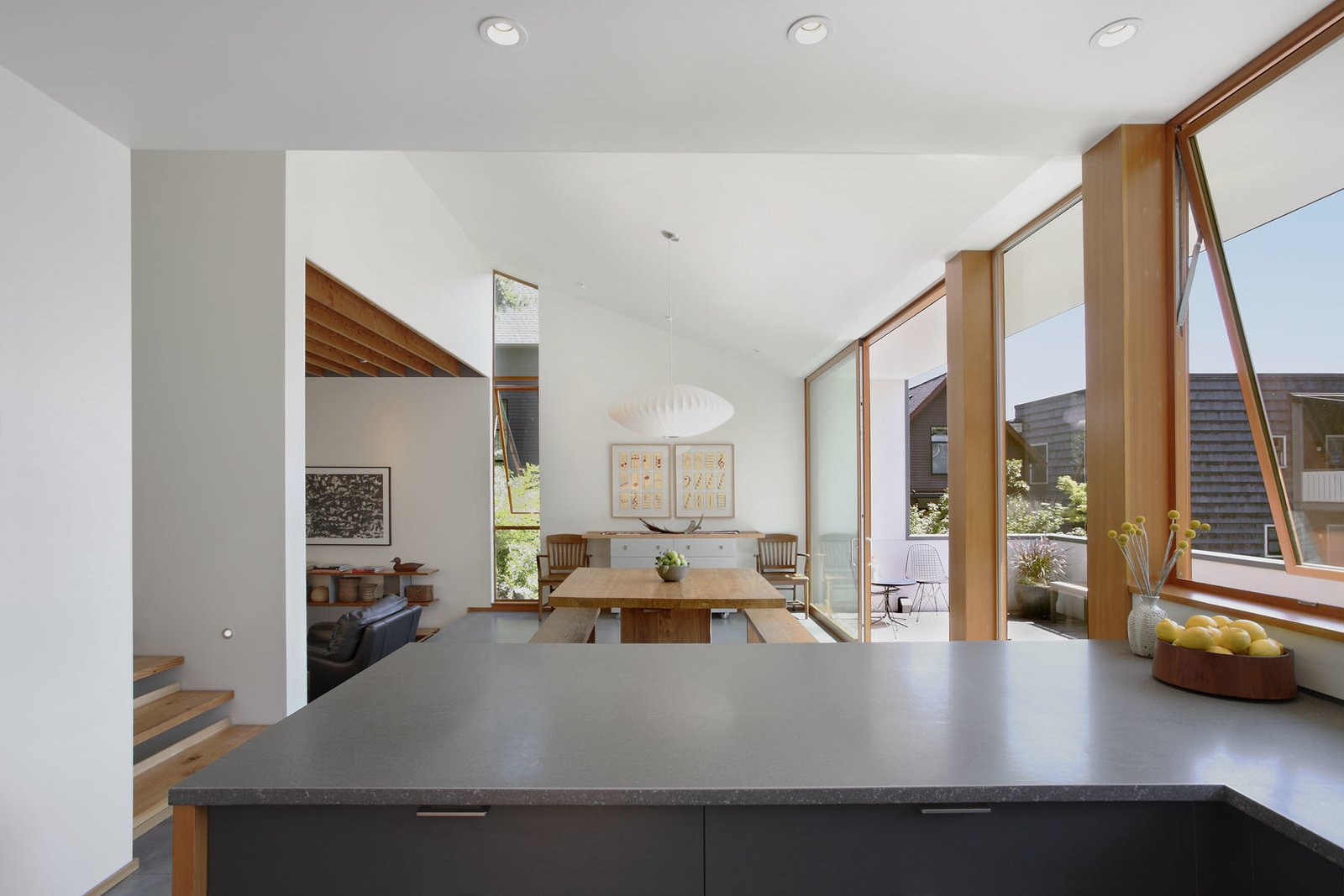"""A George Nelson Saucer Pendant hangs over the table. Behind it, a vertical slot window frames a Douglas fir tree while editing out the windows of a nearby town house. """"All the openings were composed in direct response to appealing fragments of the site and to avoid relationships that would leave the owners feeling exposed,"""" Schaer says."""