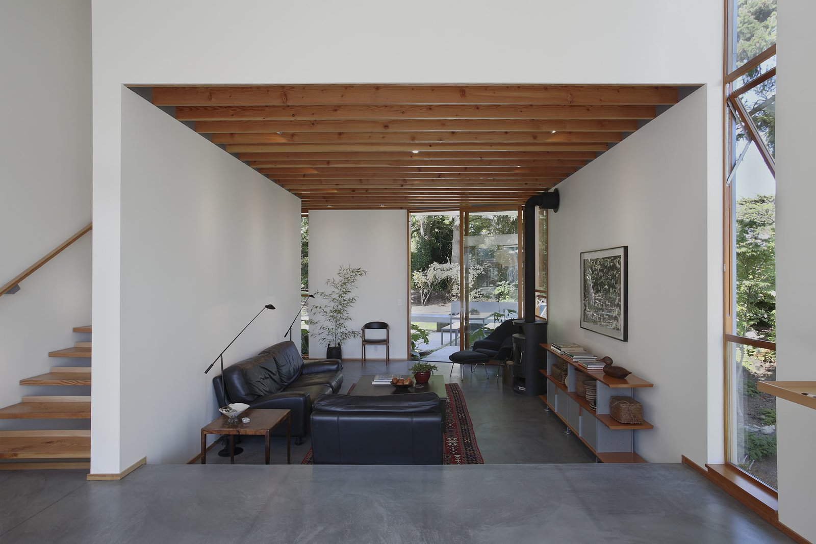 Exposed fir ceiling beams help muffle acoustics in the living room. With black leather seating, a Knoll Womb Chair and a Rais Rondo stove, the room is comfortable but sophisticated.