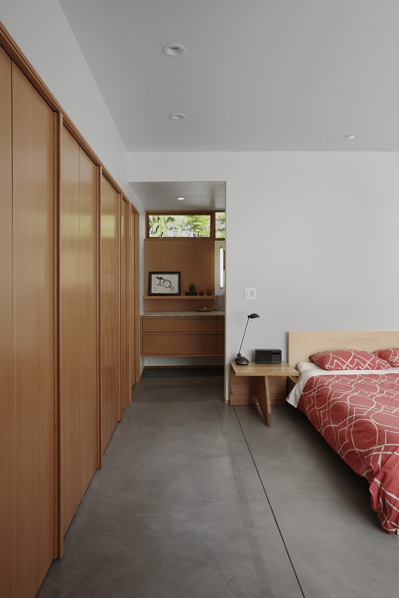 Located on the house's lower level, the bedroom is bright but soothing. The bed is flanked by custom side tables and covered with a red West Elm duvet.  Photo 6 of 11 in Seattle Home Carefully Blocks Out Neighbors, While Celebrating Natural Surroundings