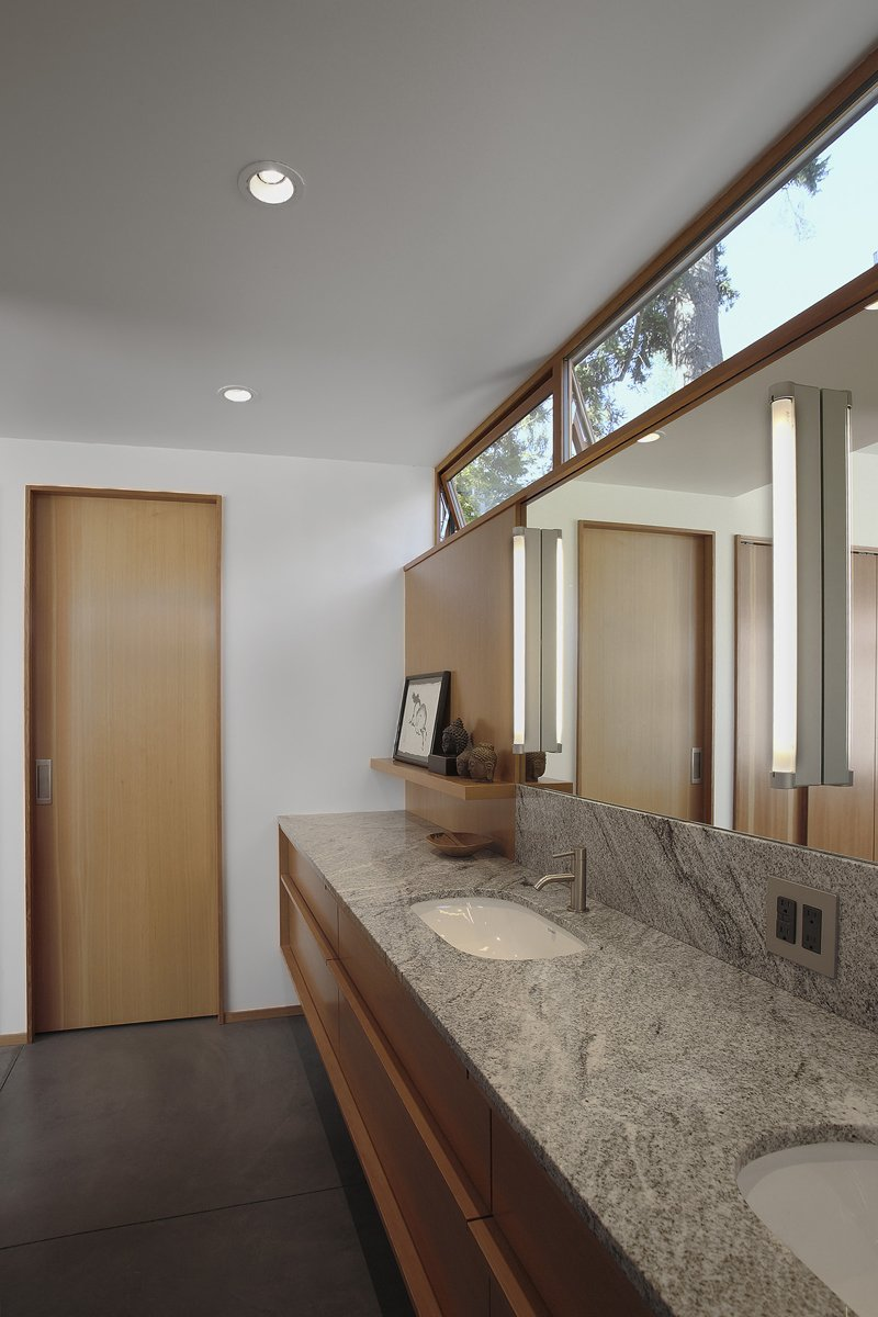 Just off the bedroom, a restrained bathroom combines Duravit D-code sinks with Techno by Cifial faucets and a Toto Aquia toilet.  Photo 7 of 11 in Seattle Home Carefully Blocks Out Neighbors, While Celebrating Natural Surroundings