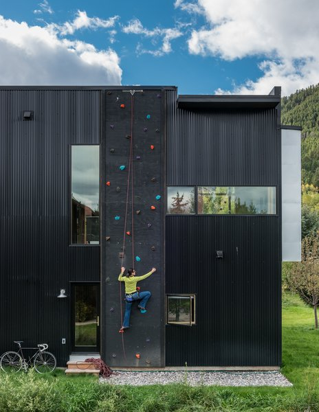 Dotted with colorful footholds, a climbing wall covers one side of the home, allowing roof access.