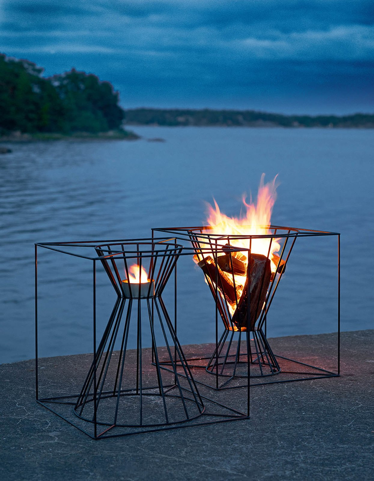 The Boo Fire Basket from Skargaarden is made of black lacquered steel. Designed to fit several logs for an outdoor fire, the Boo can also be overturned to hold a candle or lantern.  Photo 3 of 8 in Gather Around These 7 Modern Fire Pit Designs from Modern Fire Baskets for Late Summer Evenings
