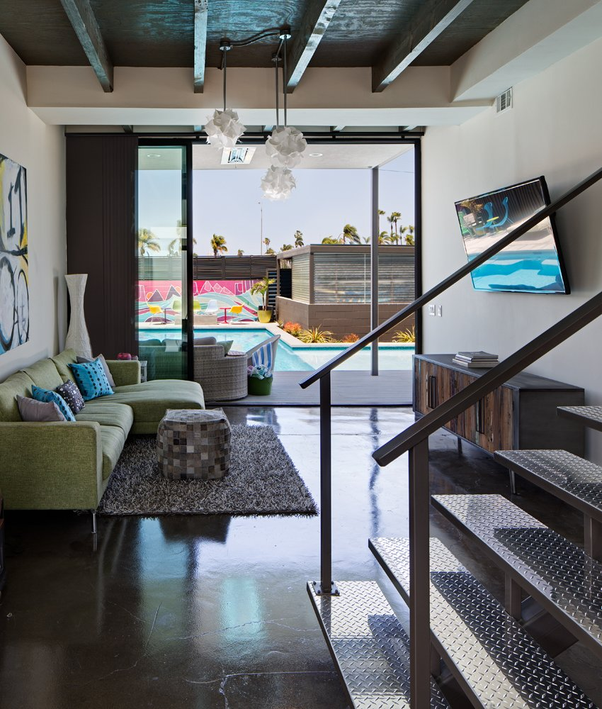 Loft-like features are used throughout the first floor interior space, including raw polished concrete floors, exposed beams (one of the few elements of the existing home that were preserved), and diamond-plate steel cladding on the floating staircase. A Dull Stucco Home Becomes a Modern California Oasis - Photo 7 of 10