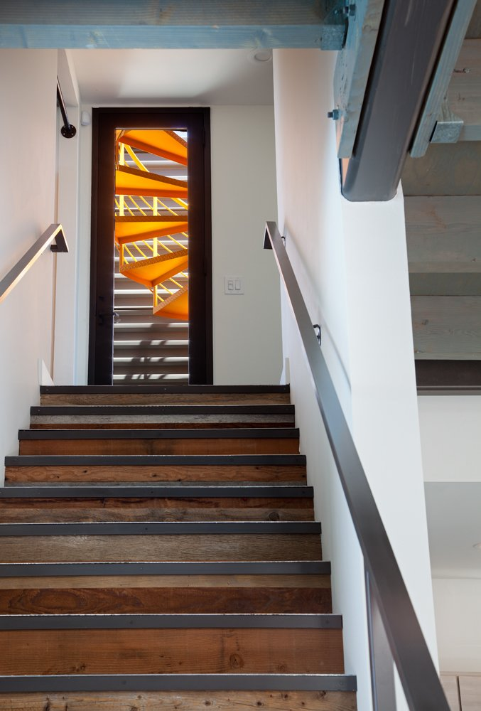 The staircase leads from the living room to an exterior balcony, where a second spiral staircase leading to the rooftop balcony was painted bright tangerine orange. The roof deck spans the entire footprint of the home.
