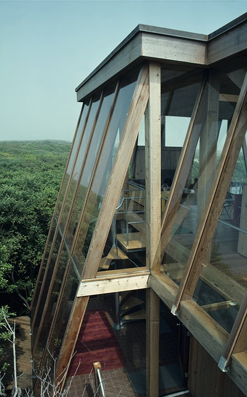 "Few architects changed the face of Fire Island as much as the midcentury master Horace Gifford. In 1975, he created this geometric glass ""tree house"" on Sail Walk, which sports screened vents between slanted glass walls and suspended floors that draw breezes through a chimney-like skylight.  Photo 2 of 6 in Take a Peek Inside a Beachside Enclave of Modernist Masterpieces"