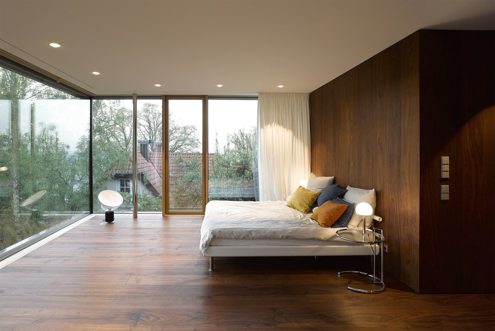 Light streams into the bedroom through walls of floor-to-ceiling glass. The windows are triple-glazed, creating a tight, eco-friendly seal.  Bedrooms by Dwell from An Uninspired Home in Germany Gets a Bright, Eco-Friendly Update