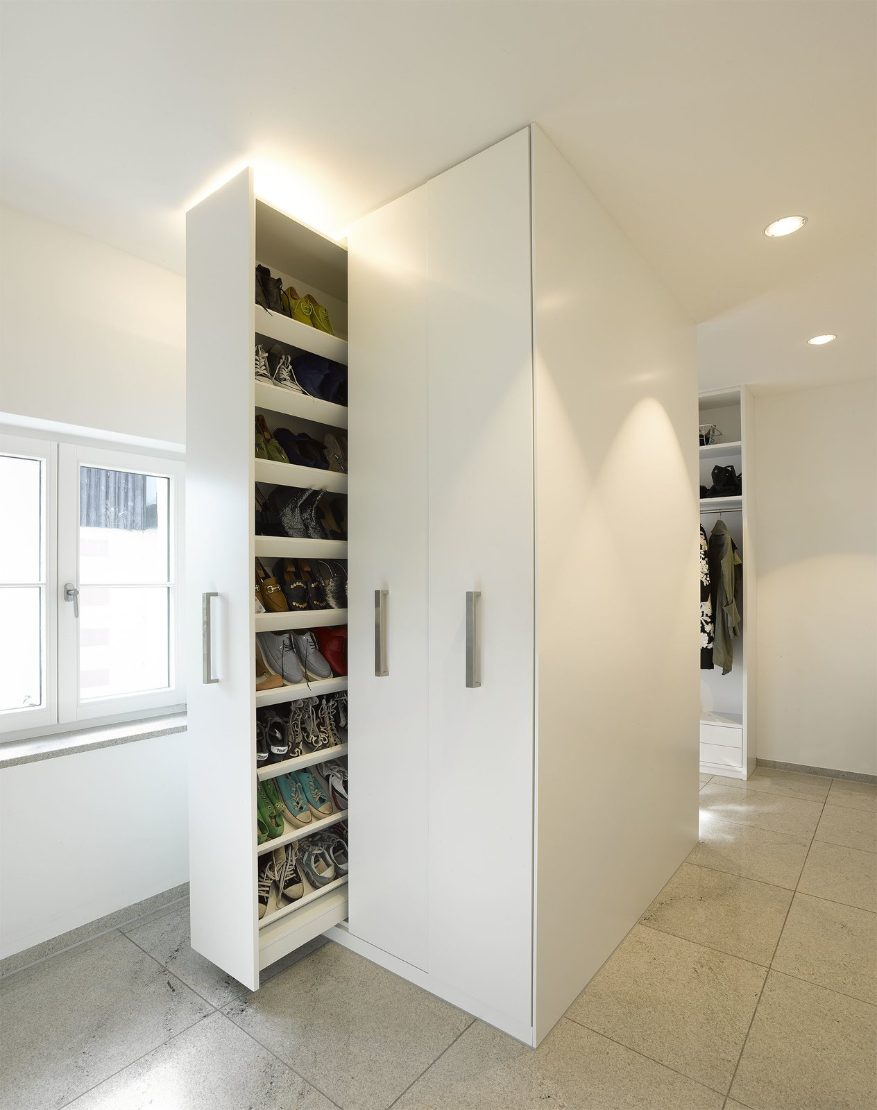 Though the home is expansive, the team made certain to waste as little space as possible. Clever moments of storage, like this sliding shoe closet, abound.  Renovations by Annette Luikart from An Uninspired Home in Germany Gets a Bright, Eco-Friendly Update