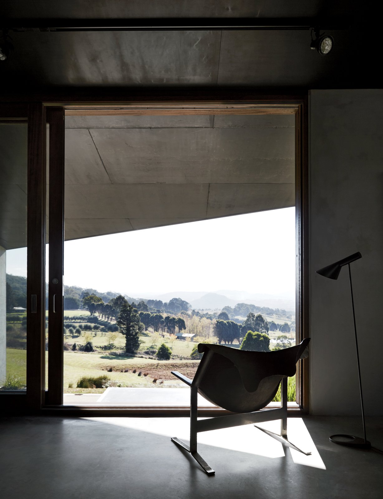 """A Clement Meadmore Sling chair provides a favorite vantage point for sipping coffee while looking out at Hanging Rock. """"It's always hard to leave and return to the city,"""" Titania says. Tagged: Living Room, Chair, and Floor Lighting.  Views by DAVE MORIN from Richly Furnished Home Frames Striking Landscape Views"""