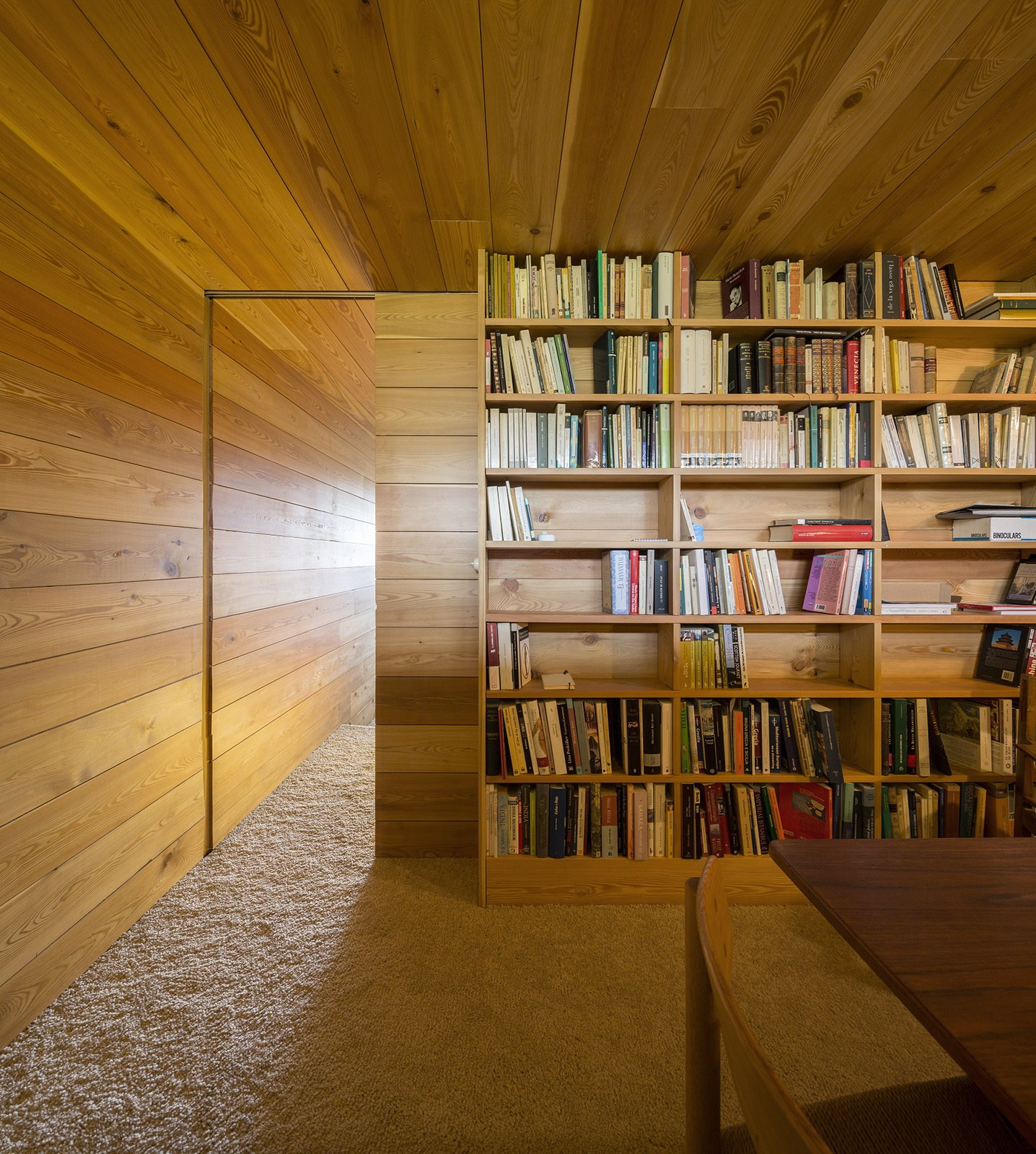 The library is accessed by a sliding wood door. Tagged: Office, Library, and Bookcase.  Refuge by Diana Budds