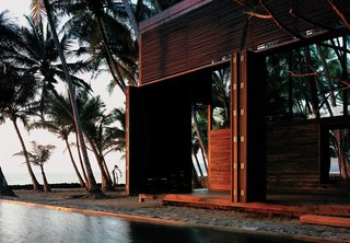 "It's hard to believe that this idyllic house sited in a coastal coconut grove in Nandgaon, India, is a mere hour's drive from bustling Mumbai. For architect Bijoy Jain, principal at Studio Mumbai Architects, making the most of the muggy locale meant foregoing walls for louvers and slatted sliding doors—and opting for local materials to construct the airy home. ""Response to weathering is critical along the seaside,"" he explains. The East Indian laurel, Burma teak, and palmyra woods will endure the seaside climate with an oiling after each monsoon. The pool that runs between the two structures of the home contrasts the choppy white-capped ocean with tranquil charm, making it a favorite spot for the vacationing family of four, who spend weekends here at the retreat."