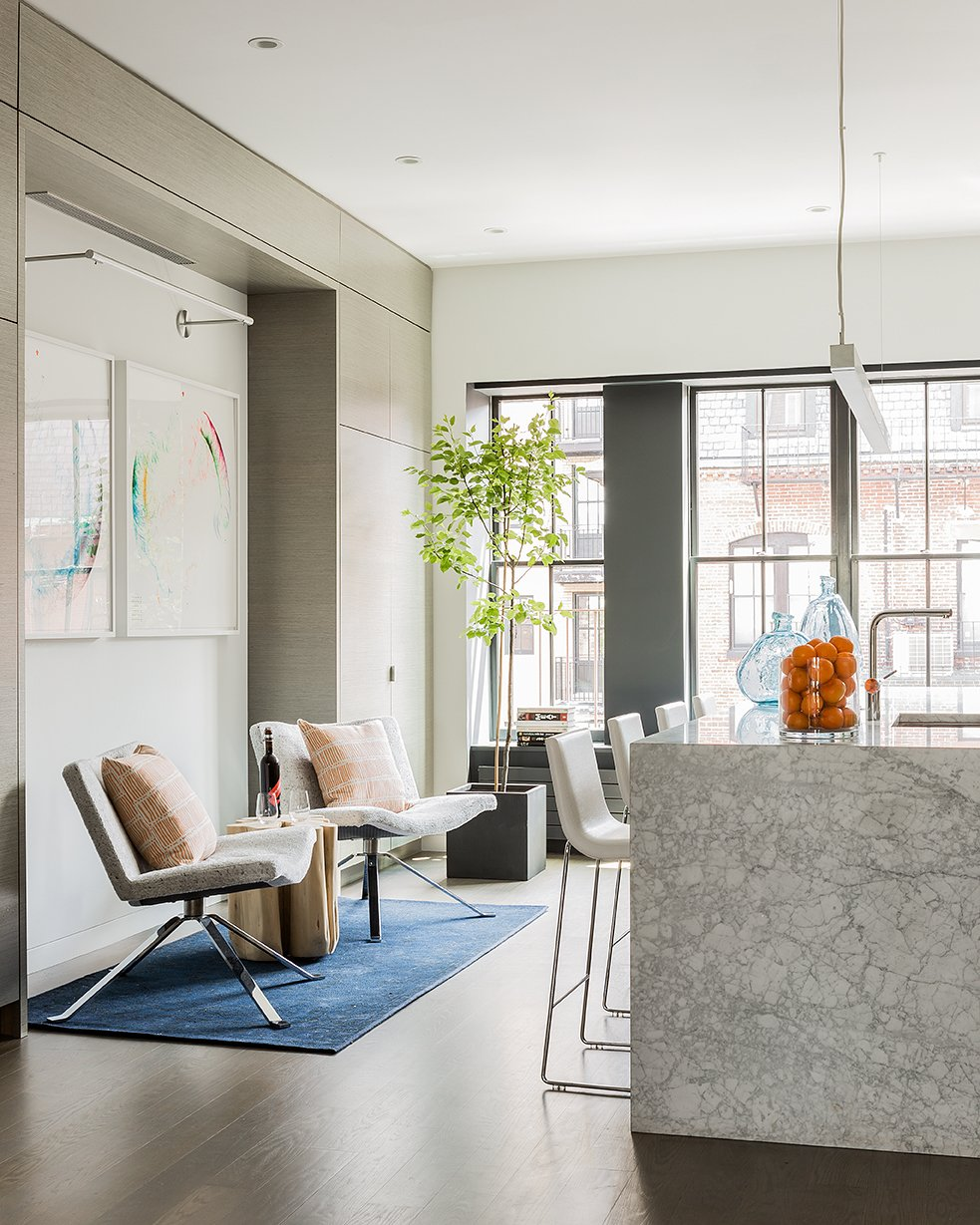 """[The owner] needed a good working kitchen, the ability to seat up to 20 at dining tables, and accommodate over 100 for cocktails and fundraisers,"" Walker said. The Tonon Wave chairs  are covered in Dalmatian upholstery by Calvin Fabrics; they sit on a Bursa Wool Rug from West Elm. Tagged: Dining Room, Chair, Stools, Light Hardwood Floor, Rug Floor, Recessed Lighting, Pendant Lighting, and Bar.  Photo 2 of 21 in Mad About Marble: 20 Kitchens and Bathrooms from Modern Spaces for Entertaining and Hosting"