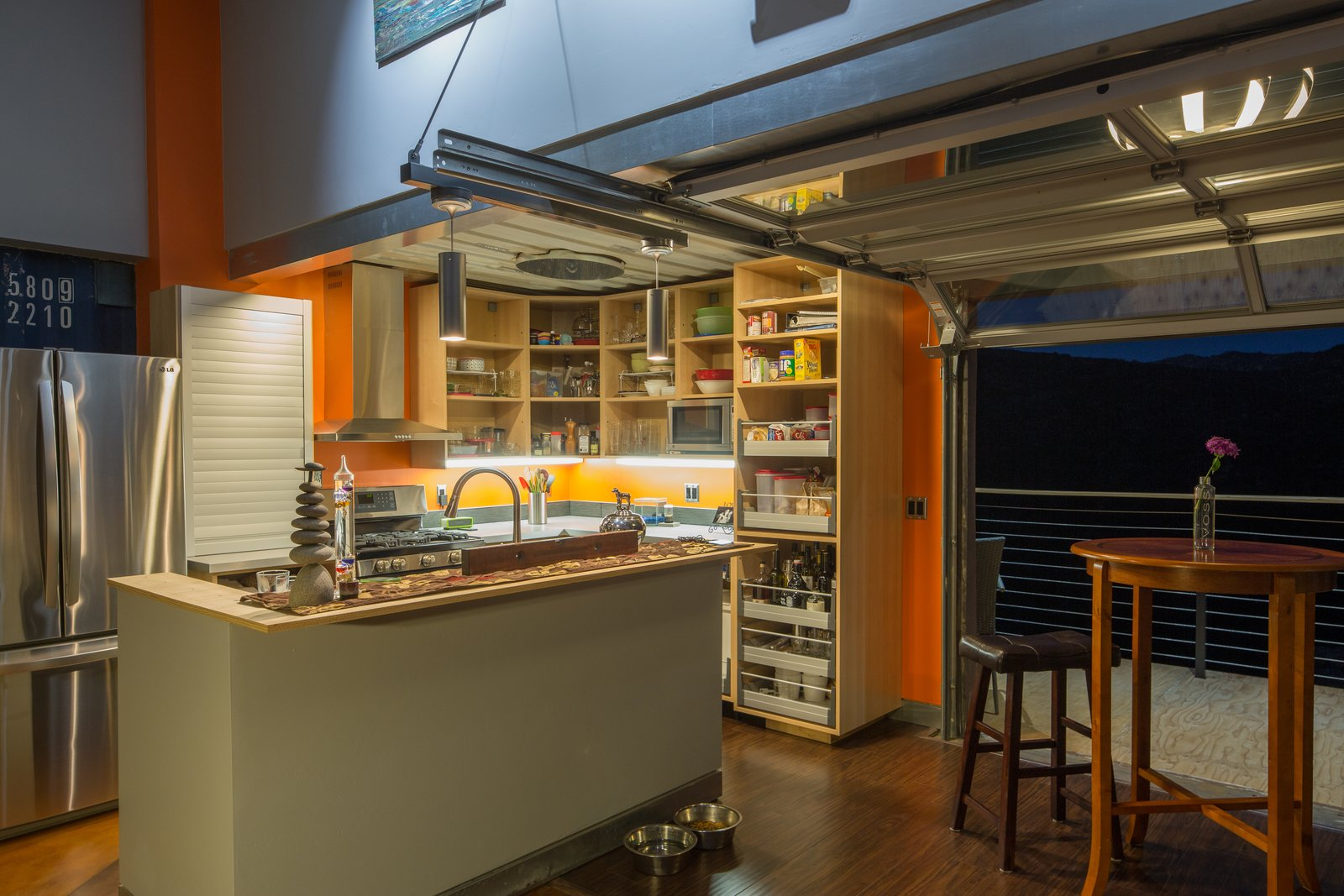 In the open-plan kitchen, a garage door can be retracted to take advantage of the balmy California climate and bring the outdoors in. Mike's wife, Shawn, appreciates the home's proximity to hiking trails.  Shipping Containers by Dwell from A Rustic Shipping Container Home Built on a Budget