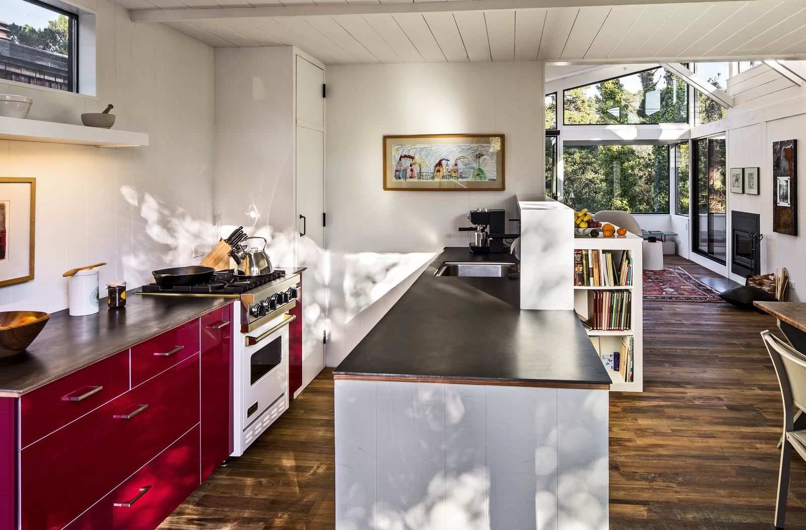 This house in Carmel by the Sea is enlivened by its very red kitchen cabinetry. By knocking down a dividing wall, the architects opened the kitchen up to the rest of the living space. Ikea red lacquer cabinetry and Caesarstone countertops replace dingy cupboards and old-fashioned finishes. Stainless steel appliances help ground the airy, open space.