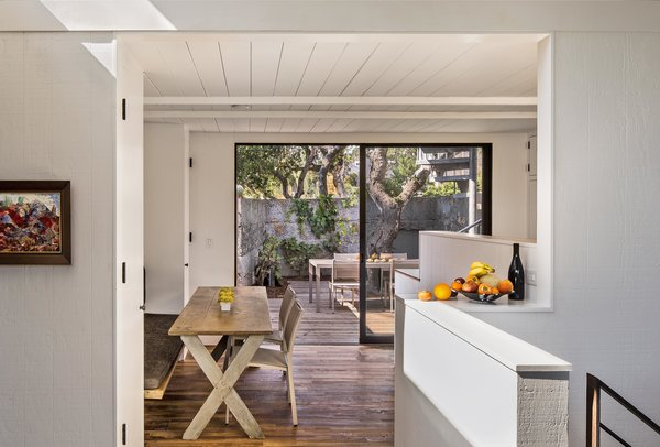 Guests now dine on a table from Coup d'Etat in the space where the residents used to enter the house. The dining room feels much larger than it actually is, thanks to a ten-foot-wide sliding glass door that opens onto a second, outdoor lounge. Photo 7 of Torres House modern home