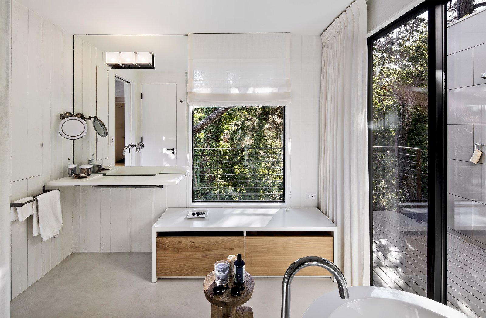 The updated master bathroom features white concrete floors, painted wood walls, and veneer plaster ceilings. Light streams in through the original window, and an added sliding door opens to an outdoor shower. A single Washplane sink by Omvivo sits beneath the mirror, with additional faucets for the shower and Duravit bathtub by Hansgrohe. A stool from Roost holds bath essentials.