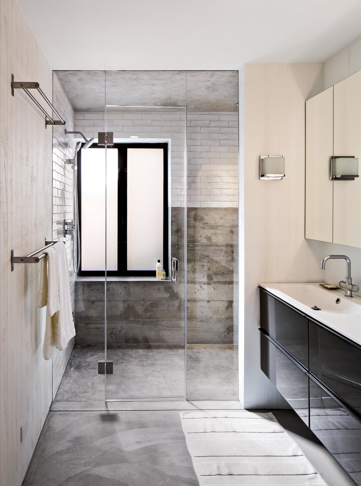 On the house's lower level, Schicketanz's guests have a bathroom complete with a steam shower to themselves. Anodized aluminum windows pop against white subway tile from Waterworks. The vanity is from Ikea and the fixtures from Hansgrohe.